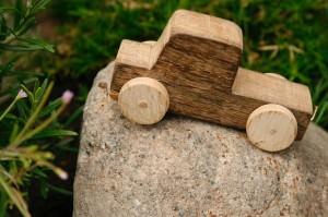 Drewniane autko-zabawka leży na kamieniu
