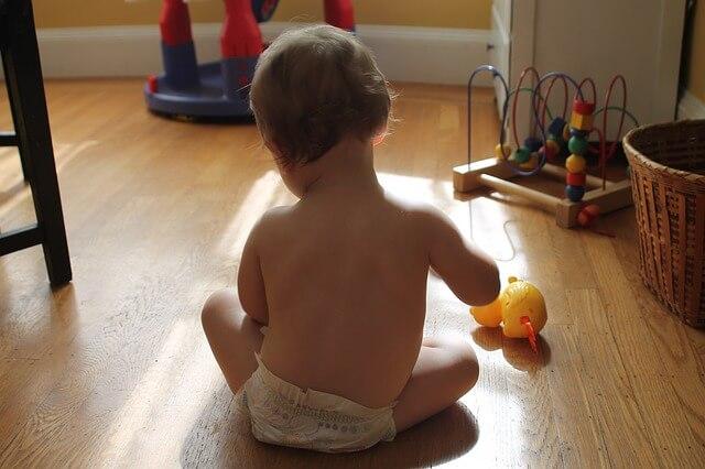 Dziecko siedzi na podłodze w pokoju i bawi się