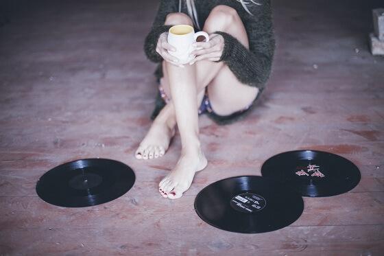 Dziewczyna siedzi na podłodze wśród winylowych płyt