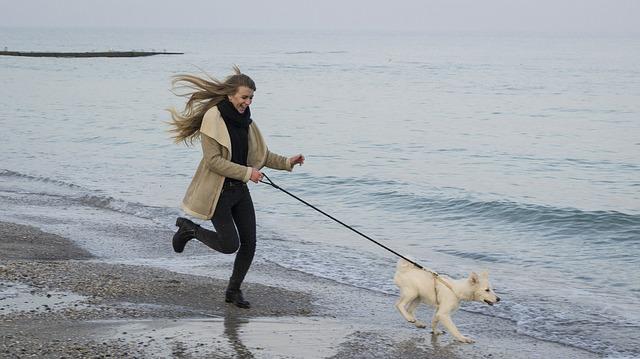 Dziewczyna biegnie z psem nad brzegiem morza