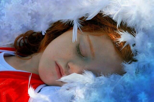 Dziewczynka śpiąca wśród piór
