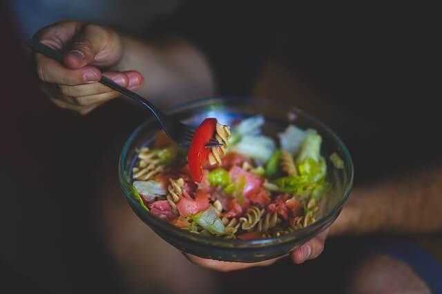 Człowiek jedzący widelcem sałatkę w misce