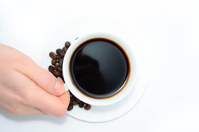 Dłoń trzyma za ucho filiżankę z kawą