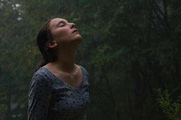 Kobieta wystawia twarz w stronę spadających kropel deszczu