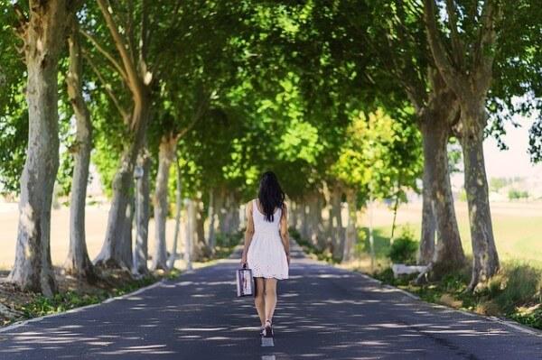 Kobieta idąca drogą pośród drzew