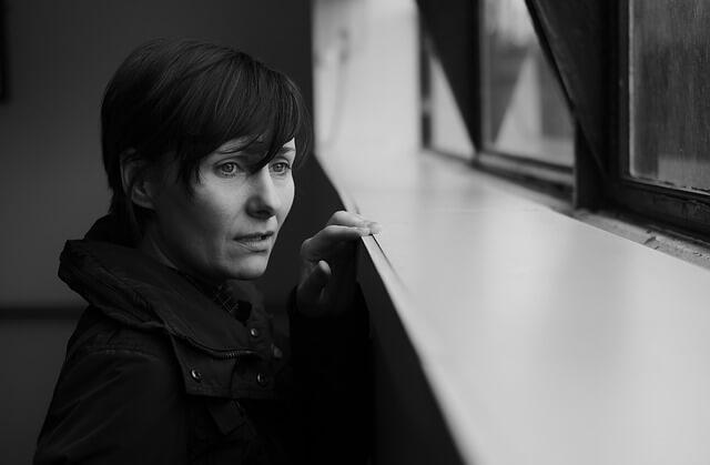 Smutna kobieta stoi przy oknie