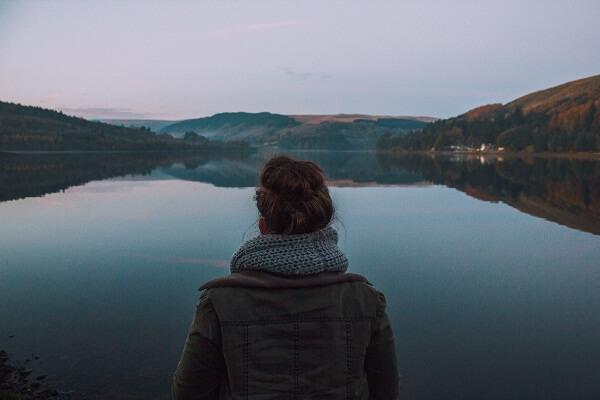 Kobieta patrzy na spokojny krajobraz z jeziorem