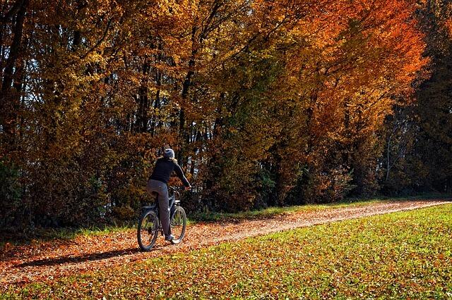 Kobieta jadąca jesienią na rowerze
