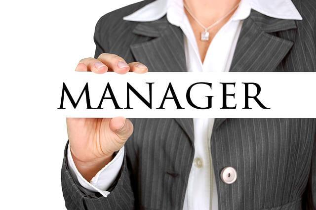 """Kobieta w marynarce trzyma w ręce napis """"Manager"""""""