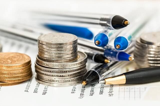 Monety, długopisy leżące na papierach wartościowych