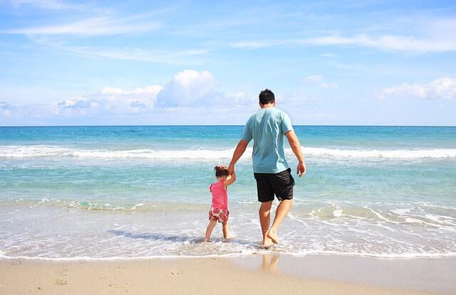 Ojciec z dzieckiem spacerują nad brzegiem morza