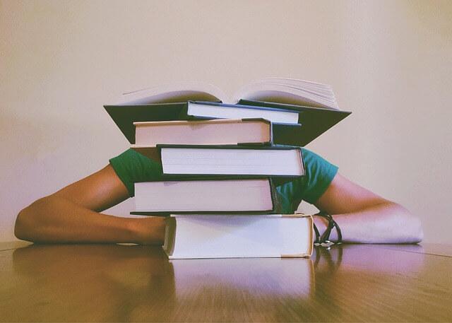 Student siedzący za stertą książek