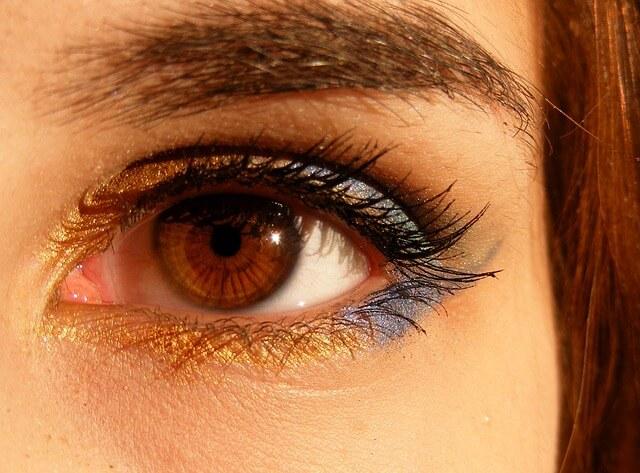 Oko rozświetlone złoto-fioletowym cieniem