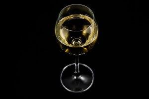 Białe wino w kieliszku na czarnym tle