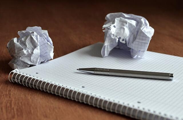 długopis, notatnik i pomięte kulki papieru