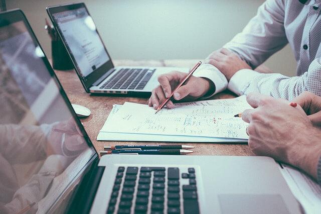 Dwaj mężczyźni wspólnie tworzący dokument przy biurku