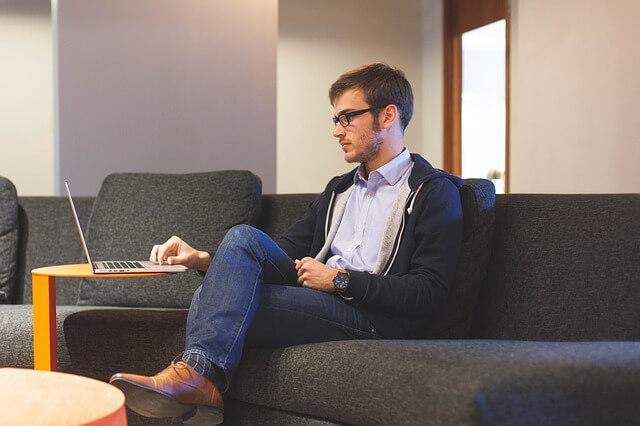 mężczyzna z laptopem na kanapie