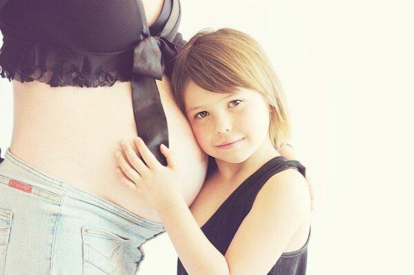 Dziewczynka przytula się do ciążowego brzucha